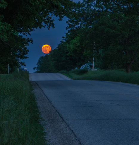 Super-moon rising over a country road Waterloo, Ontario Canada