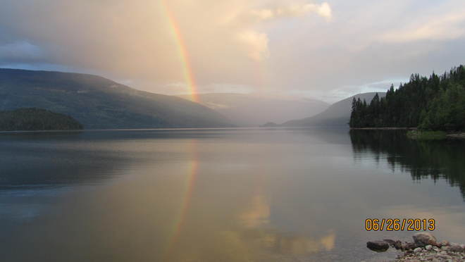Pink hue evening rainbow on lake Cherryville, British Columbia Canada