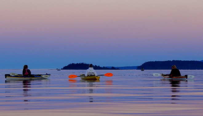 Kayaking trio wait for the full moon to rise. Royston, British Columbia Canada