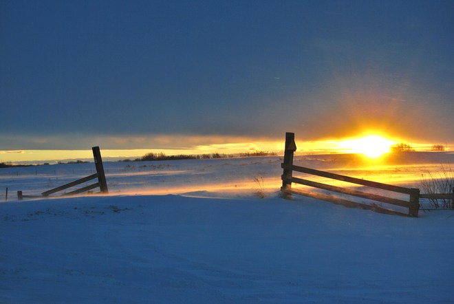 sunset on fence and blowing snow Unity, Saskatchewan Canada