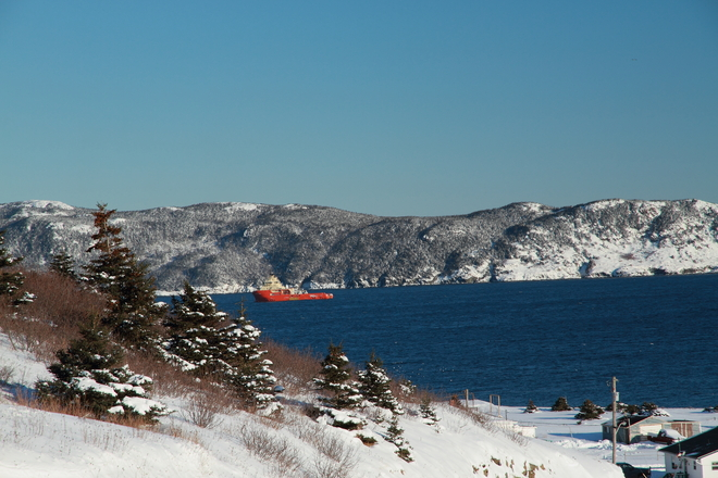 Ship escorting oil rig out to sea as seen from the beach hill on Bell Island Bell Island, Newfoundland and Labrador Canada