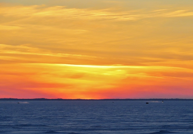 Cold weather sunset as ice fishermen head home. North Bay, Ontario Canada