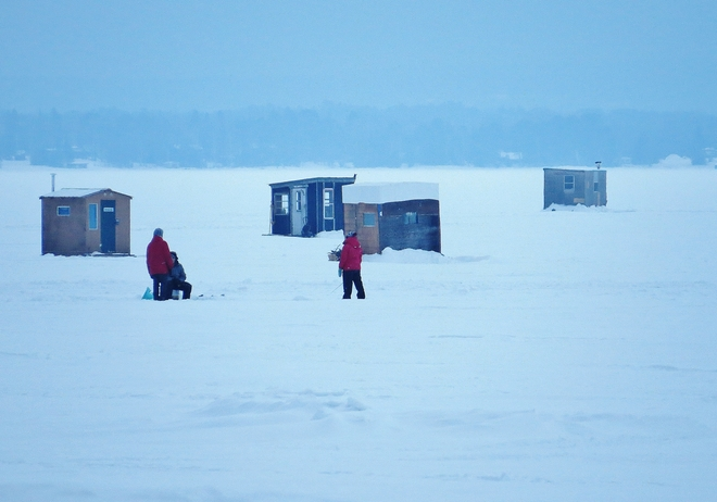 Ice fishing on a mild, hazy evening. North Bay, Ontario Canada