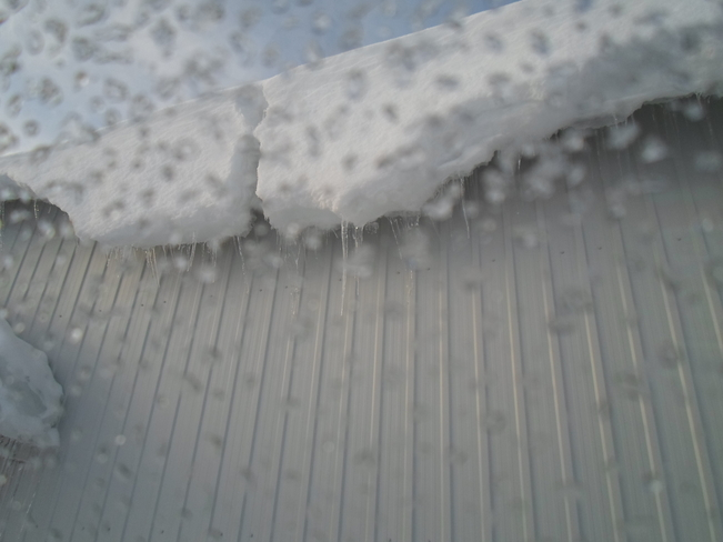 Snow and ice hanging off a roof E.L Elliot Lake, Ontario Canada
