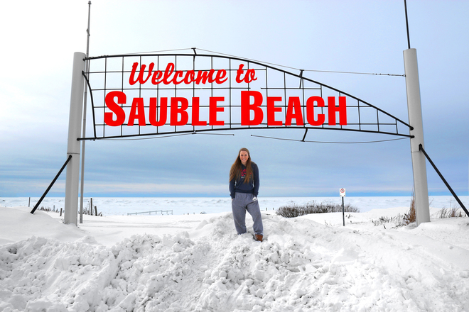Teenage girl stands under Sauble Beach sign! Sauble Beach, Ontario Canada