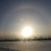 Couché de soleil entouré d'un arc-en-ciel