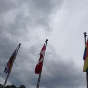 Three flags outside City Hall under clouds