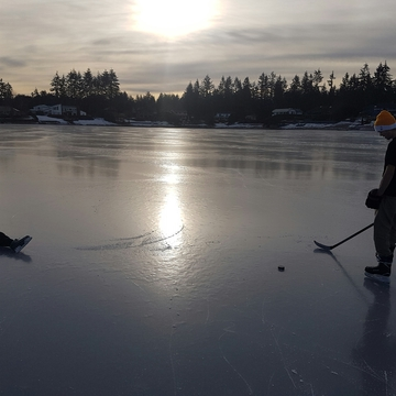 Brothers on the lake playing hockey