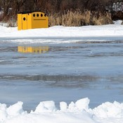 Yellow shed by frozen lake on a beautiful winter day