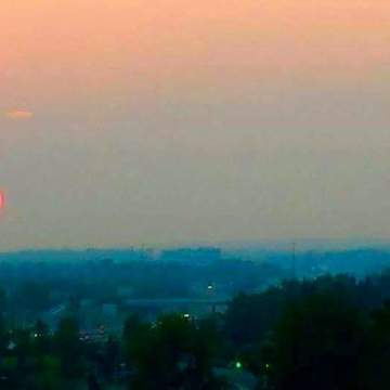 The sun looked very round and red with the background of smoky air from forest d