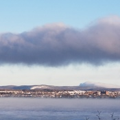Three clouds on and over the Ottawa River looking over the Gatineau hills.