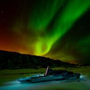 Traditional Qamitiq sled under Northern Lights