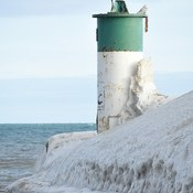 Snowy owl perched on lighthouse