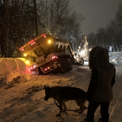 a snow removal truck slides in a ditch.