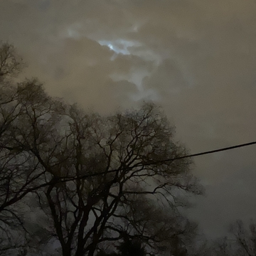 Remnants of Super Worm Moon behind Clouds