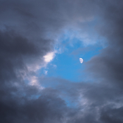 Half moon in between rain clouds